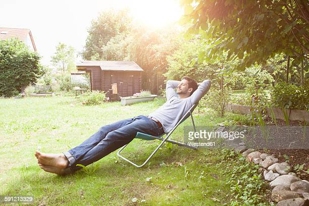 man relaxing in garden chair - outdoor chair stock pictures, royalty-free photos & images