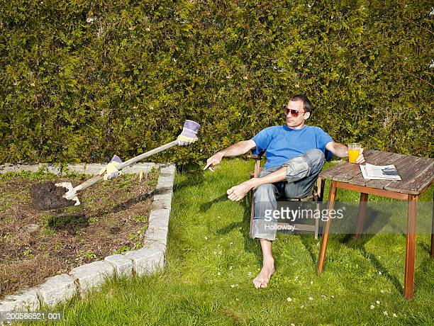 Man relaxing in garden, commanding to invisible person working with shovel (digital composite)