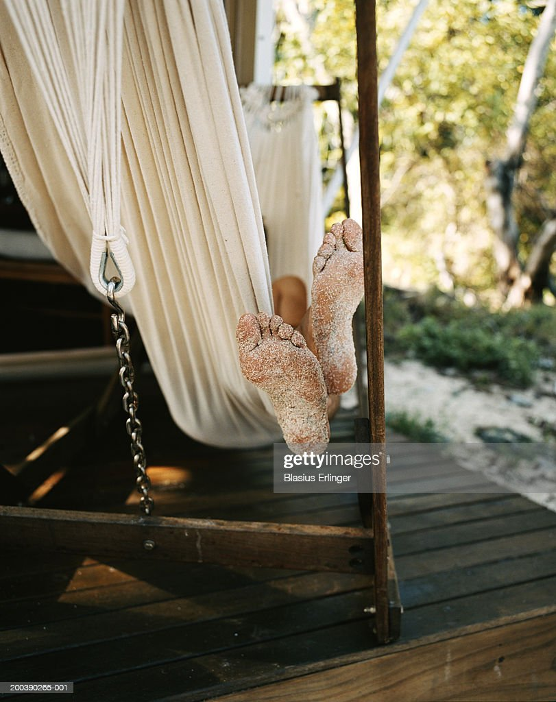 Man relaxing in hammock at beach bungalow, low section : Stock Photo
