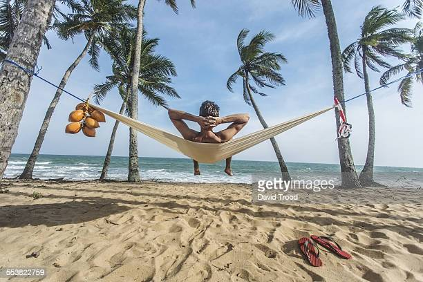 Man relaxing in hammock on the beach.