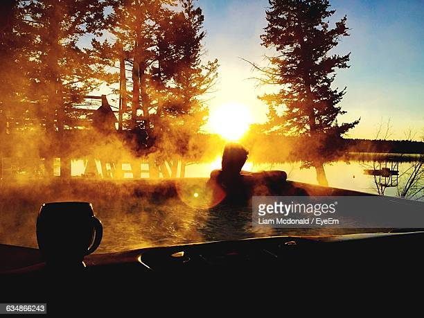 Man Relaxing In Hot Bathtub At Lakeside During Sunrise