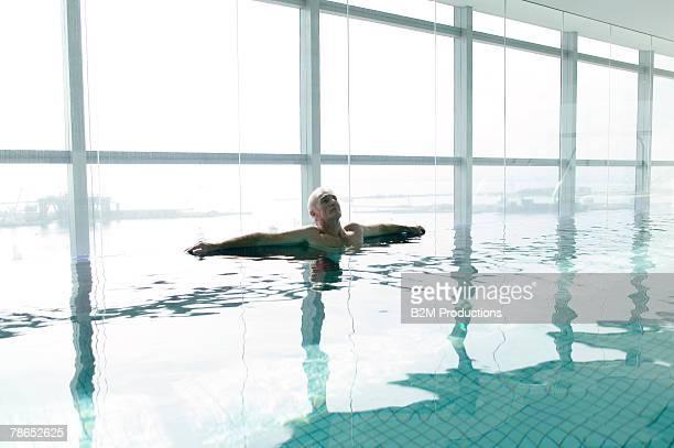 Man relaxing in indoor pool