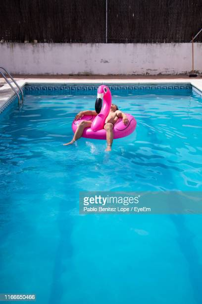 man relaxing in inflatable ring on swimming pool - rubber ring stock pictures, royalty-free photos & images
