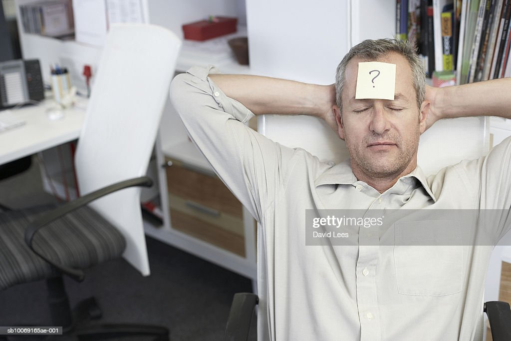 Man relaxing in office with question mark written on adhesive note stuck to forehead : Stockfoto