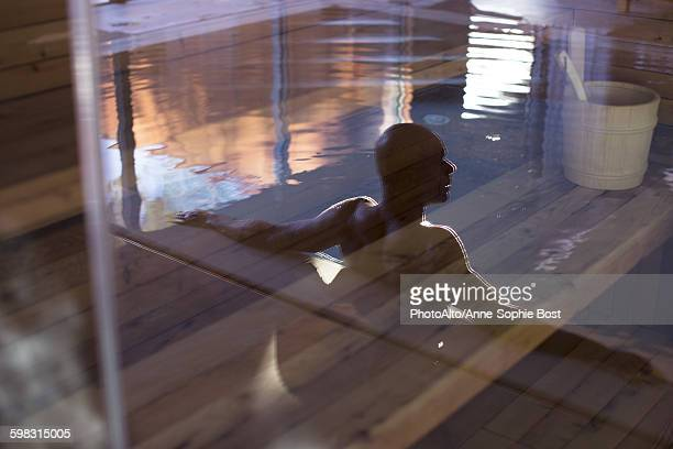 man relaxing in swimming pool, reflected on glass door - leisure facilities stock pictures, royalty-free photos & images