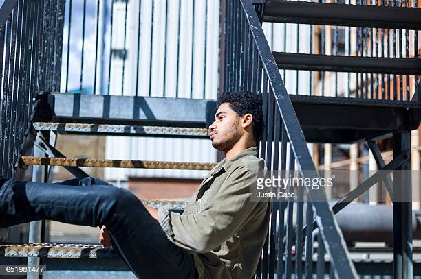 Man relaxing in the sunshine on fire stair case