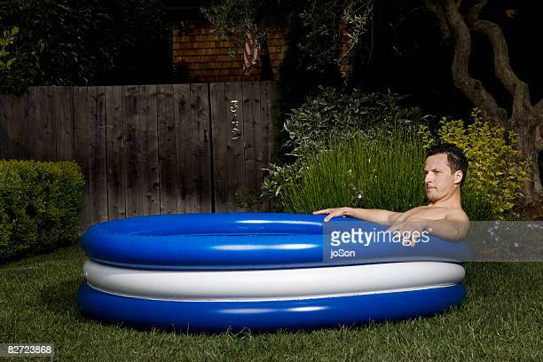 Man relaxing in vinyl kiddie paddling pool