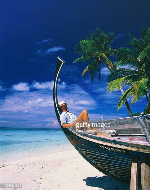 Man relaxing in wooden boat on tropical beach