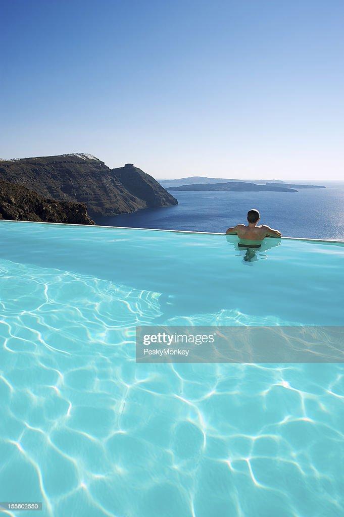 Man Relaxing Looking at Santorini Caldera from Infinity Pool