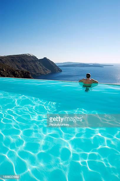 Mann entspannenden Blick auf Santorin Caldera vom Infinity-Pool aus