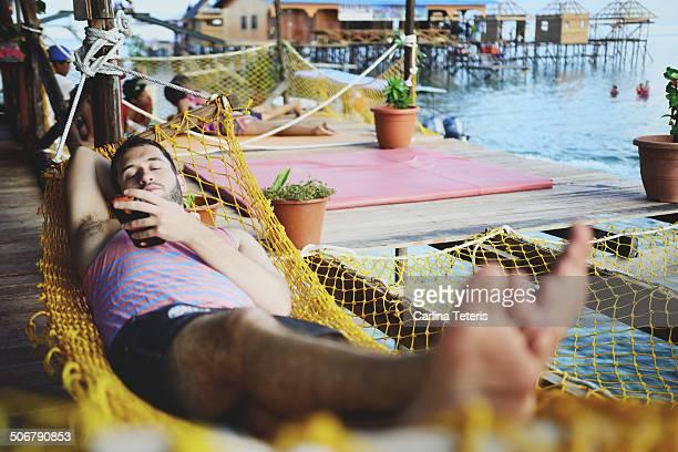 man relaxing on a hammock - ilha de mabul imagens e fotografias de stock