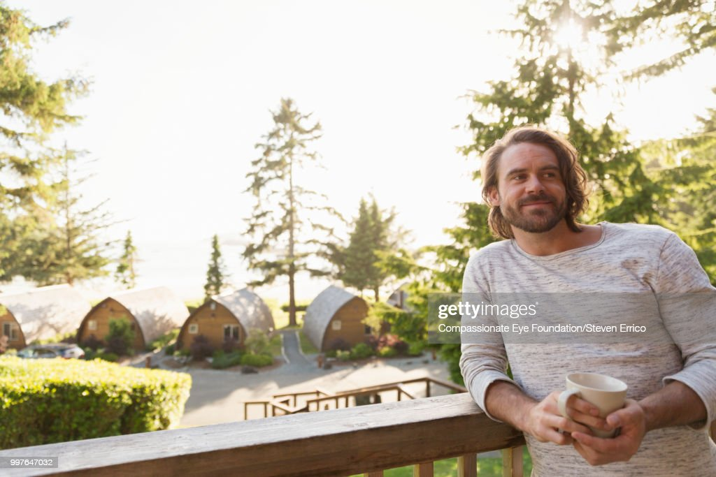 Man relaxing on balcony at holiday village : Stock Photo
