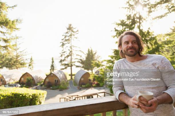 Man relaxing on balcony at holiday village