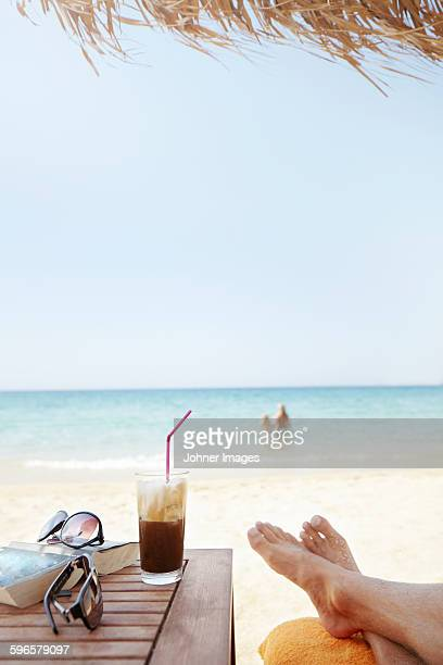 man relaxing on beach - naxos stockfoto's en -beelden