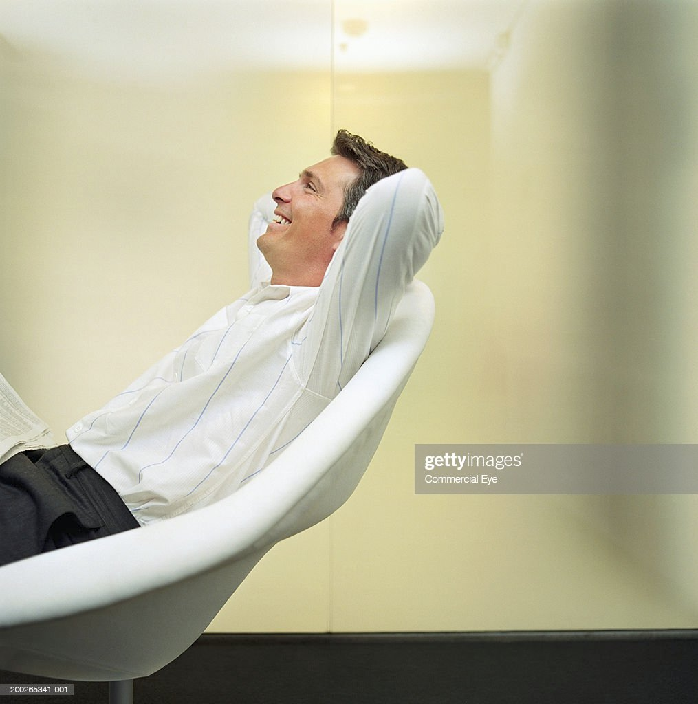 Man relaxing on chair, arms behind head, side view : Stock Photo