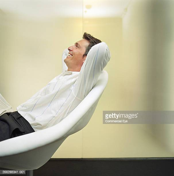 Man relaxing on chair, arms behind head, side view