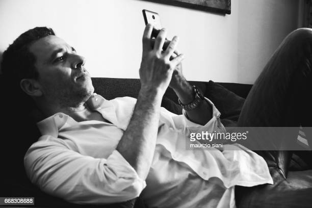Man relaxing on couch using cell phone