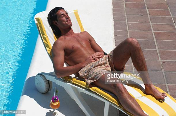 Man relaxing on deck chair by pool