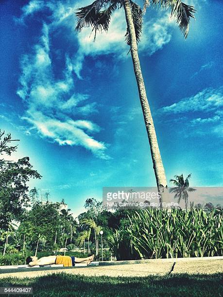 Man Relaxing On Field By Coconut Palm Tree Against Sky