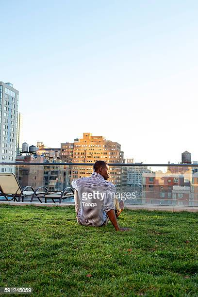 Man relaxing on grass on top of building
