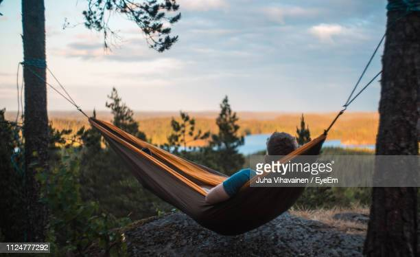 man relaxing on hammock against landscape - hammock stock pictures, royalty-free photos & images