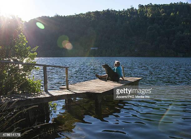 man relaxing on lake pier with dog, sunrise - pucon fotografías e imágenes de stock