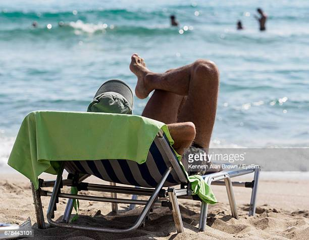 Man Relaxing On Lounge Chair At Beach