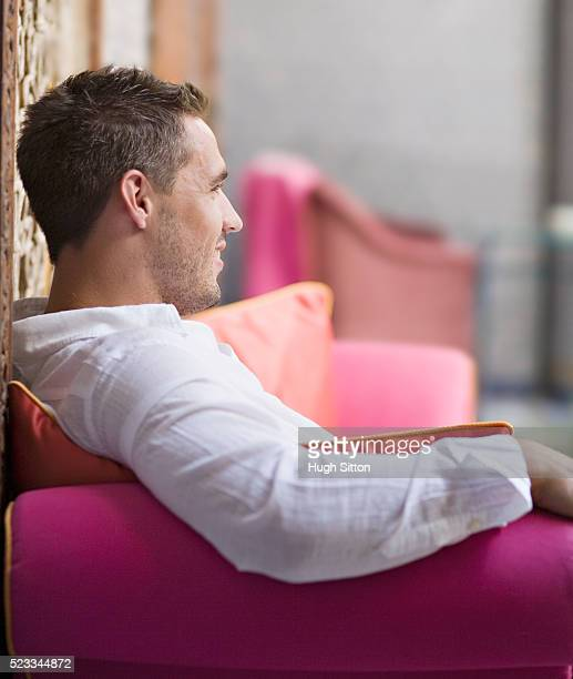 man relaxing on pink sofa - hugh sitton stock pictures, royalty-free photos & images