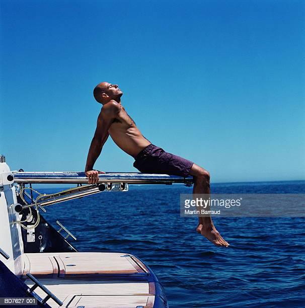 man relaxing on platform at back of speed boat, profile - homem moreno imagens e fotografias de stock