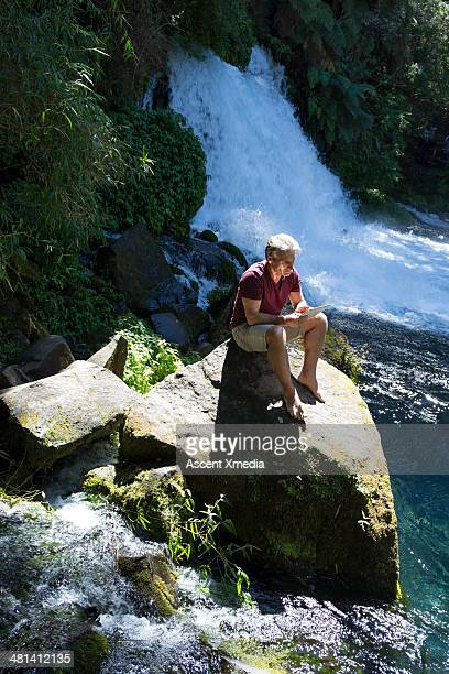 Man relaxing on rock above creek