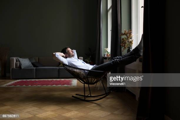 Man relaxing on rocking chair in his living room