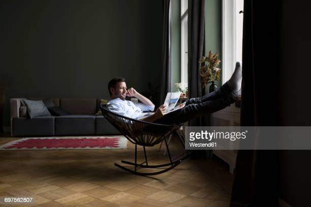 Man relaxing on rocking chair in his living room reading newspaper