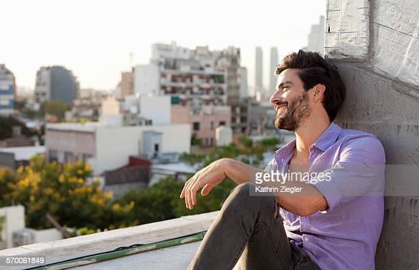 man relaxing on rooftop, enjoying the view