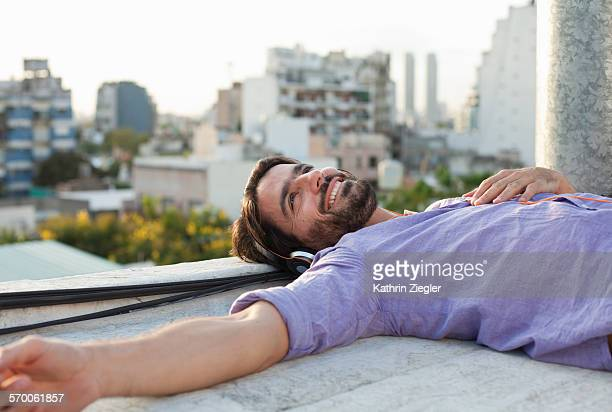man relaxing on rooftop, listening to music