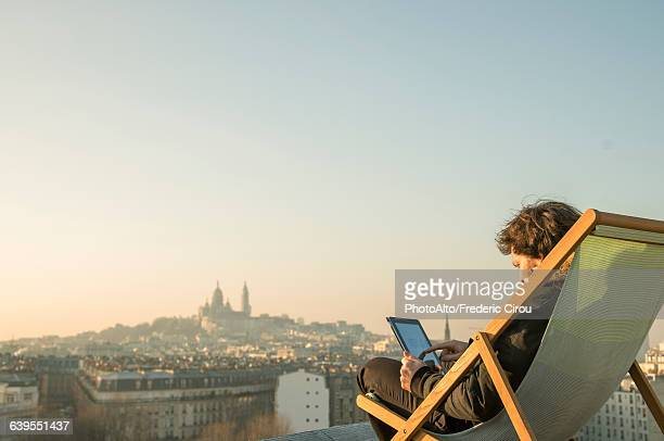 Man relaxing on rooftop terrace with digital tablet