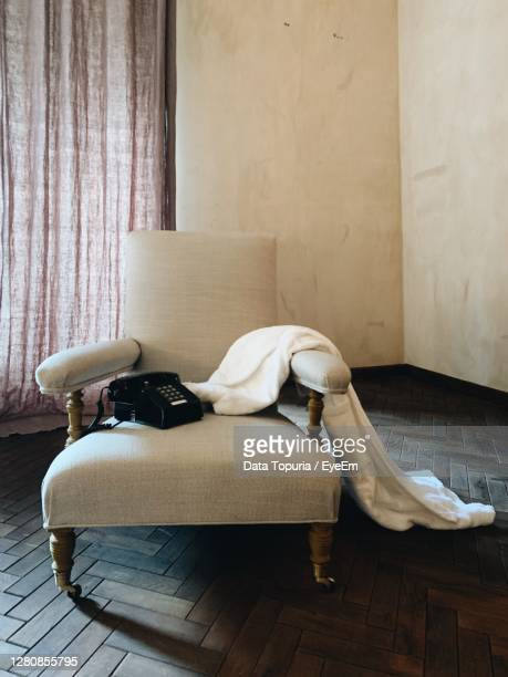 man relaxing on sofa against wall at home - data topuria stock pictures, royalty-free photos & images
