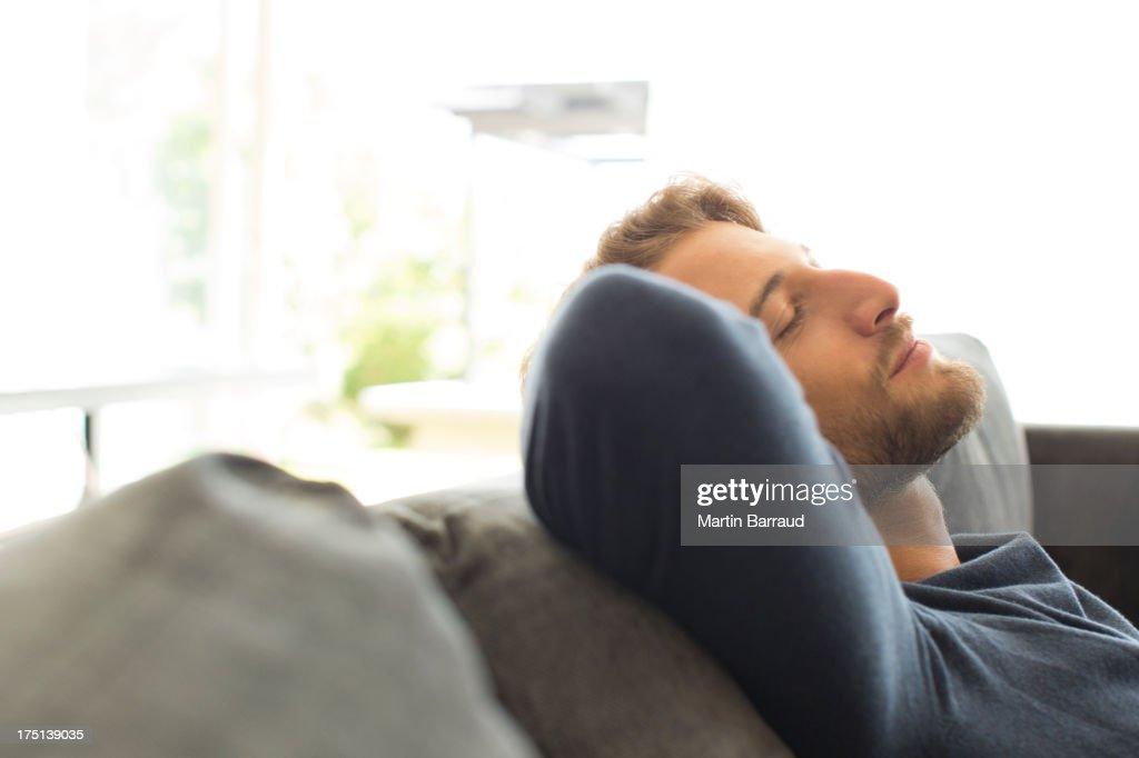 Man relaxing on sofa : Stock Photo