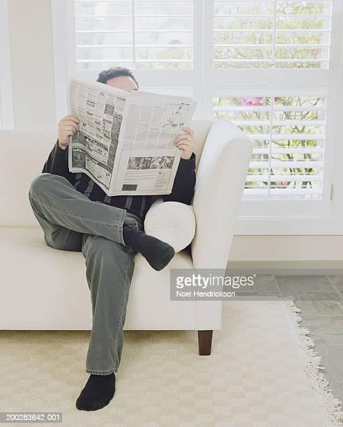 man relaxing on sofa reading newspaper - viso nascosto foto e immagini stock