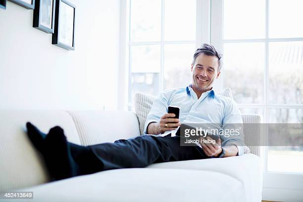 man relaxing on sofa using digital tablet and smartphone - 男性一人 ストックフォトと画像