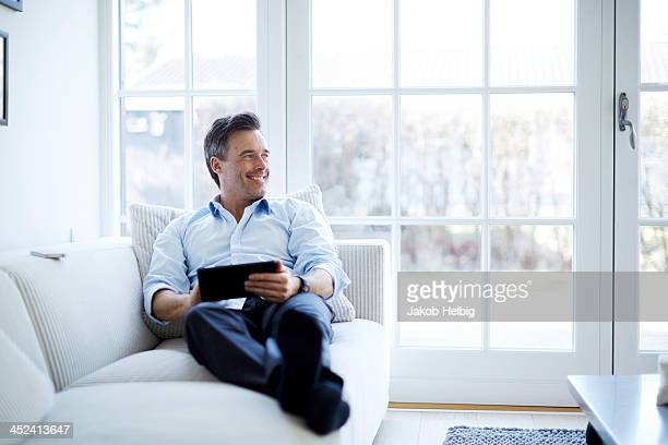 Man relaxing on sofa using digital tablet