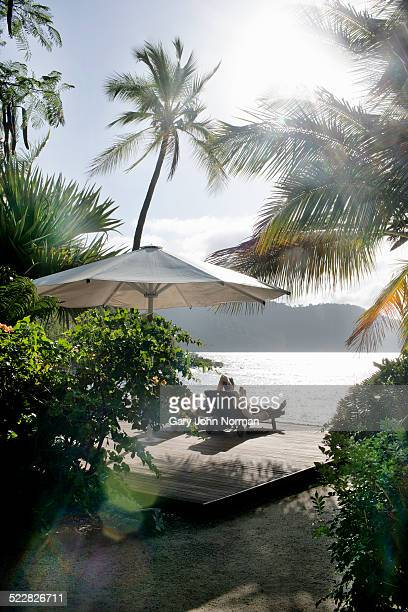 Man relaxing on sun lounger on tropical island.