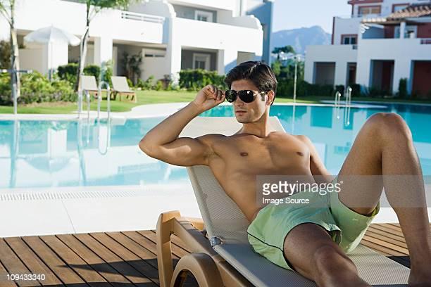Homme détente sur sunlouger au bord de la piscine