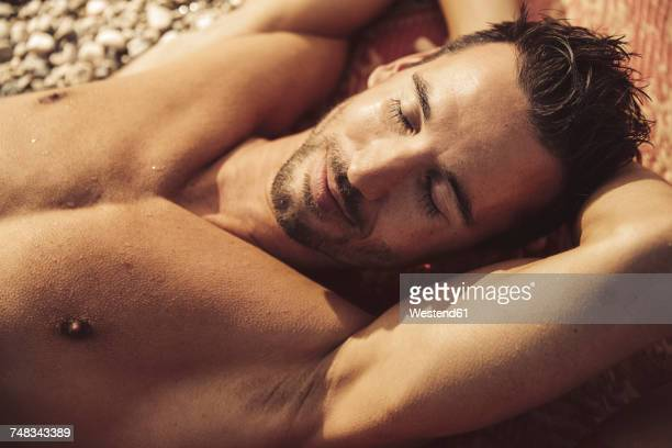 man relaxing on the beach - homem moreno imagens e fotografias de stock