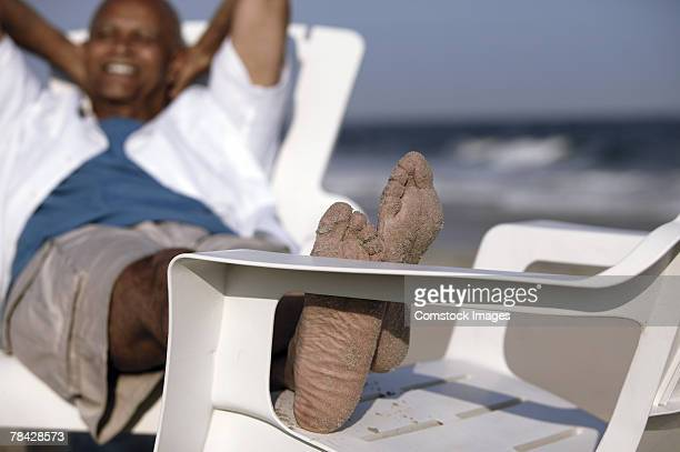 man relaxing on the beach - black men feet stock photos and pictures