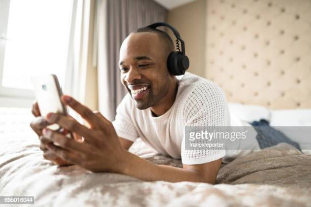 man relaxing on the bedroom with headphone - photo messaging stock photos and pictures