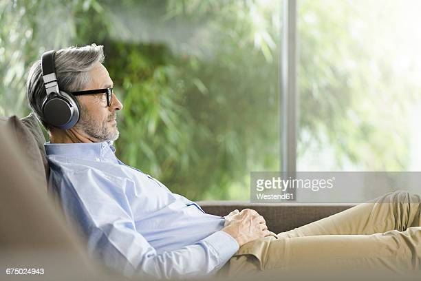 man relaxing on the couch listening music with headphones - only mature men stock pictures, royalty-free photos & images