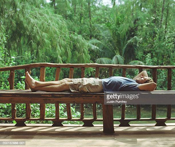 man relaxing on wooden bench on veranda, side view - エコツーリズム ストックフォトと画像