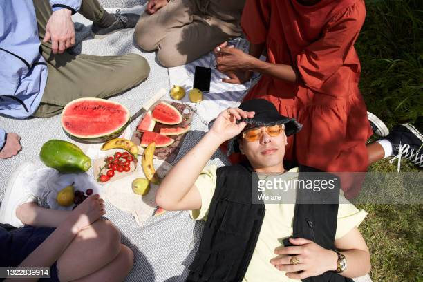 man relaxing with a group of friends enjoying a picnic - sunglasses stock pictures, royalty-free photos & images