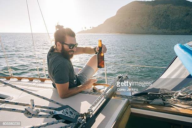 Man relaxing with beer on sailboat, San Diego Bay, California, USA
