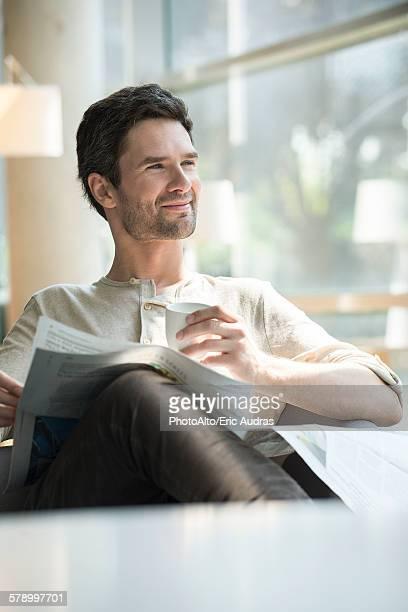 Man relaxing with coffee and newspaper